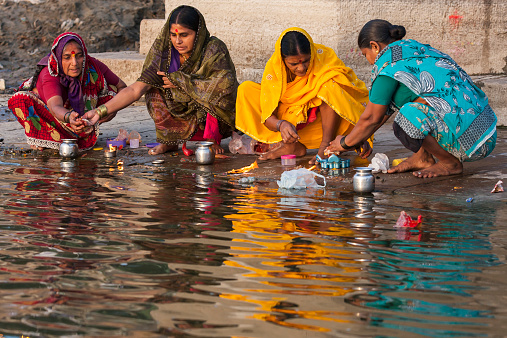 Indian women in traditional dress making offerings at the Ganges River